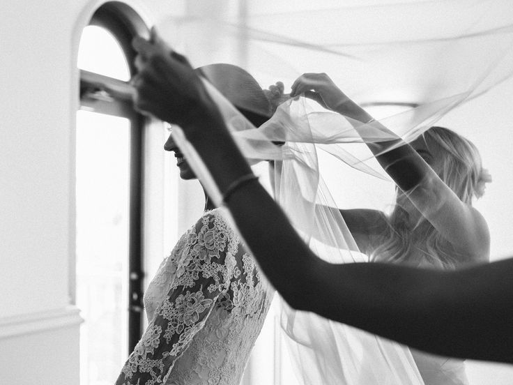 Connie Peterson and Matthew Pavlovich's Greek Wedding in Los Angeles. Pictured here is the bride getting ready for her big day. Timeless and classic, her wedding gown featured lace details and a long veil.