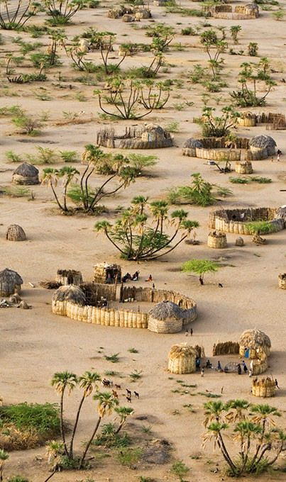 Village near Lokwakangole, Kenya, on the shores of Lake Turkana, with its woven palm-frond homes by Michael Poliza