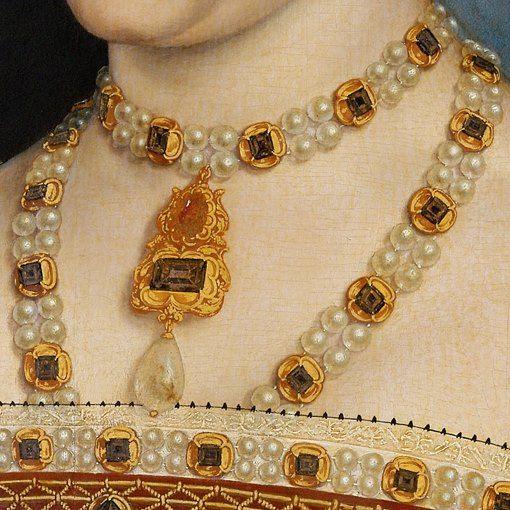 Particolari numero 4. Hans Holbein il Vecchio: Jane Seymour, regina d'inghilterra. Tempera all'uovo su tavola del 1536-37. Kunsthorisches Museum, Vienna. Il ricchissimo collier di oro, perle e pietre preziose a doppio giro, con pendente d'oro, pietre preziose e perla a goccia, finisce all'interno del bordo del vestito: anch'esso ha una decorazione simile, uguale alla collana.