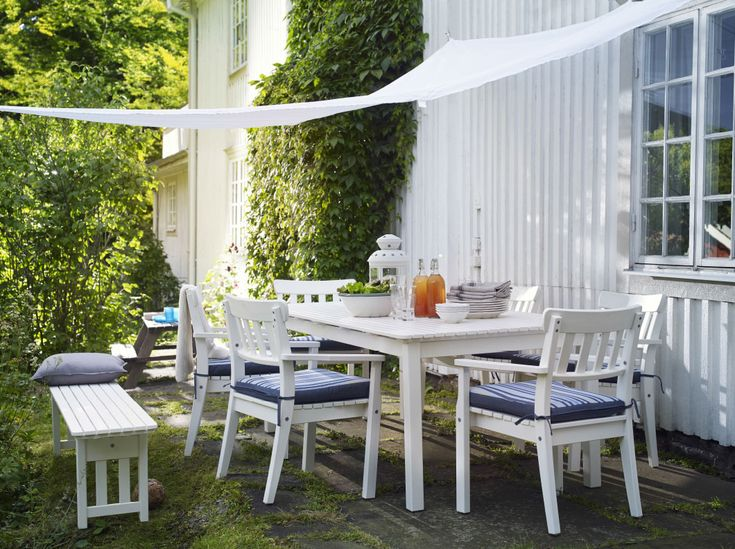 A large garden with a white suite of garden furniture consisting of a long table and six armchairs. Completed with blue striped chair cushions and a white wedge-shaped canopy.