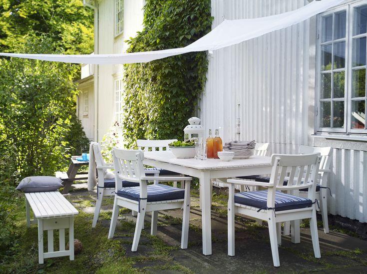 Jardim grande com conjunto de móveis para exterior em branco, que inclui uma mesa grande e seis poltronas. Complementado com almofadas para cadeiras em azul, às riscas e um dossel branco