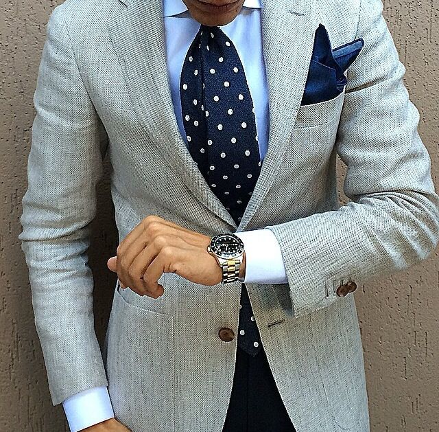 Light grey jacket, light blue shirt, navy tie with white polka dots, navy pants
