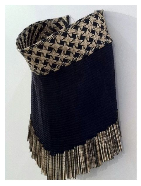 'Matariki' by Veranoa Hetet. A reversible cloak made entirely of flax (unprocessed, piupiu and fibre). The top woven panel has the Matariki pattern on one side and Waahi rua on the reverse. Both patterns represent those who have passed on. When wearing this cloak one is embraced by them. The piupiu at the bottom gives weight to the cloak and represents the gifts handed down by our ancestors - anchoring Māori in tradition.