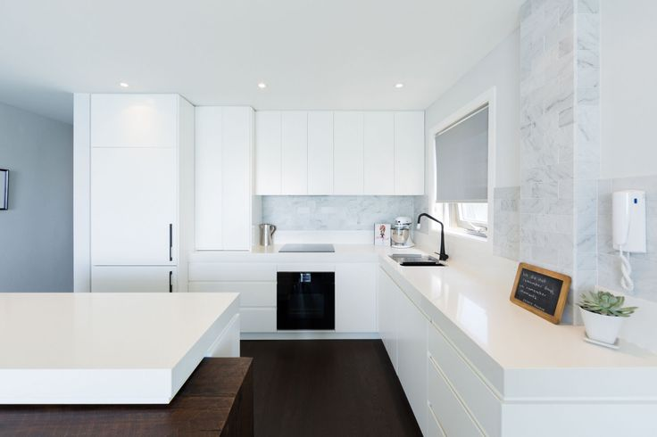 Coastal Home Kitchen by White Door Design with 90mm Caesarstone Snow benchtops. Photos: Alex Gunawan