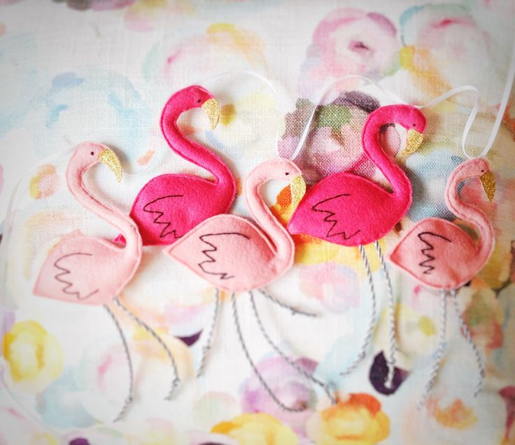 Pink flamingo garland, five hangings birds with gold glitter beaks Ideal for a little girl's room this flamingo bunting features five handmade felt flamingoes with monochrome cord legs and gold glitter beaks. Made from baby pink and fuchsia felt, with hand stitched wings, these flamingoes hang from double sided white satin thread and make a lovely newborn gift or a special addition to a nursery. Completely handmade to order and customisable. These flamingoes can be hung horizontally or…