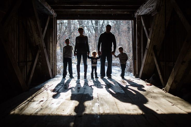 Silhouette of a family. Pictures outside with a family of five with little boys and a little girl in the woods by a covered bridge with snowy backgrounds. The Harshbarger family had a fun time playing in the snow outside making for beautiful candid moments by Rockford IL Portrait Photographer, Mindy Joy Photographer.