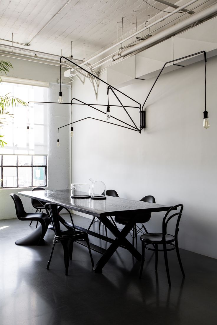 To create a place where employees and visitors can have lunch family style, they brought in a large dining table by James Perse. The hanging light is the Lampada 046 by Dimore Studio.