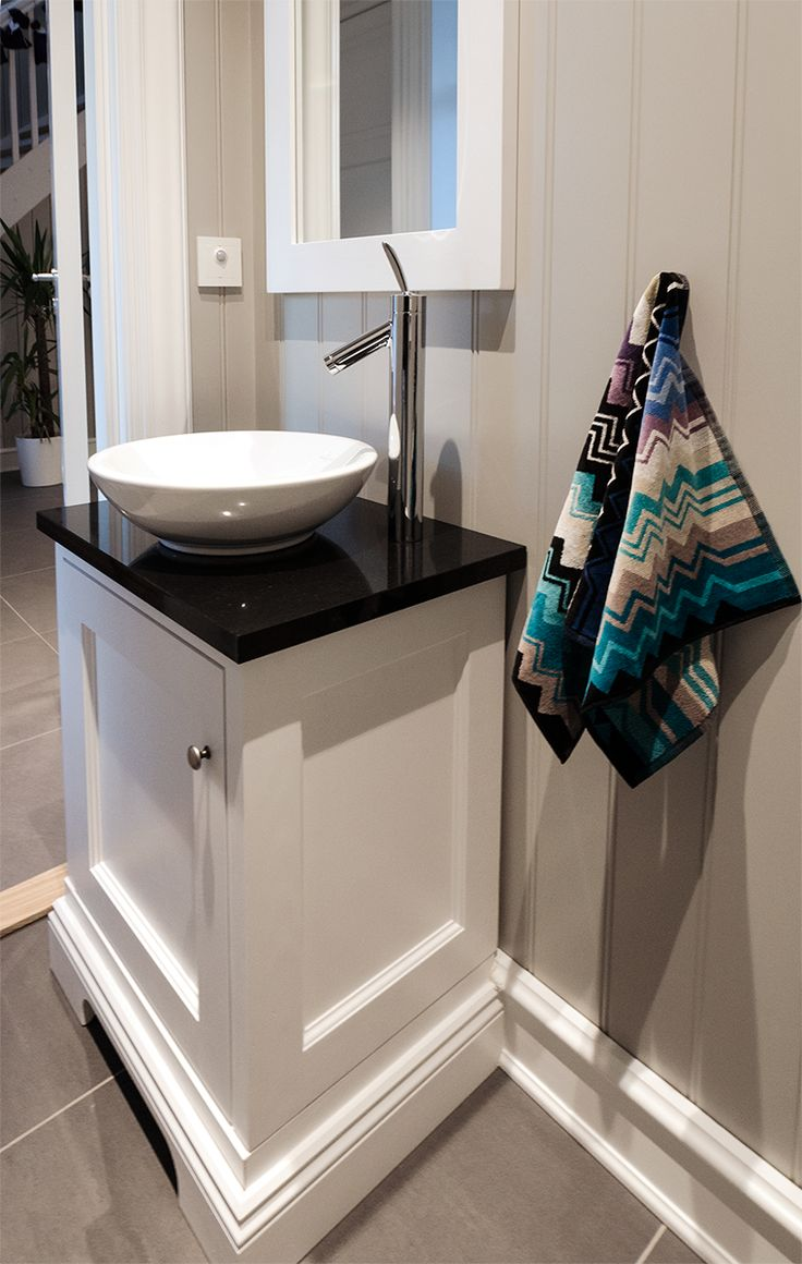 Small, white bathroom furniture with surface-mounted washbasin, and black granite countertops. Hand crafted by Os Trekultur