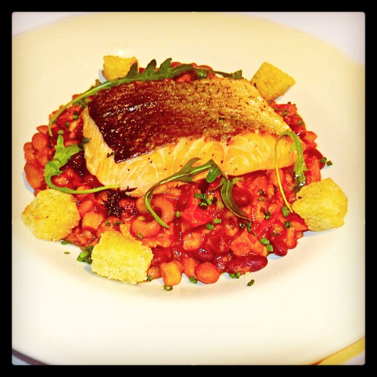 Lost River Salmon: 6oz. grilled salmon fillet, resting on a delicious spiced mixed bean & tomato stew, with saffron, bacon, chorizo, olives, rocket leaf & garlic croutons.