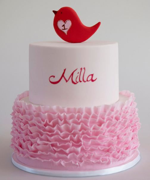 Two tier round elegant modern white first birthday cake with pink ruffles and red bird on top for girl