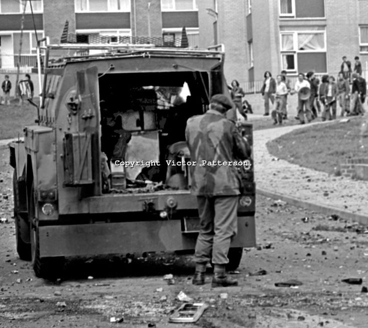 A British soldier shelters from rioters' missiles behind an armoured personnel carrier in the Lenadoon Avenue area, of Belfast, N Ireland, U...