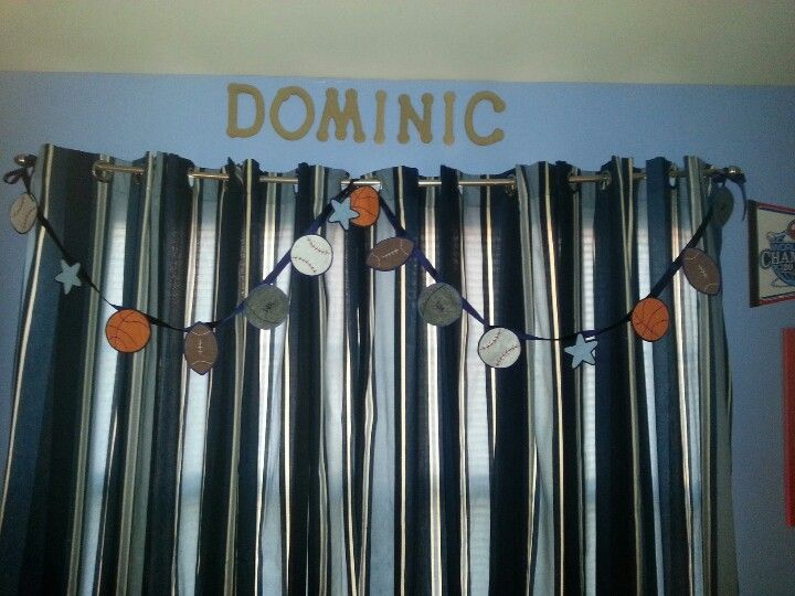 Handmade felt sports themed garland hanging above window curtains.