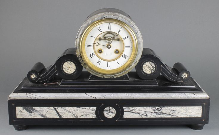 Lot 755, A Victorian French 8 day striking mantel clock contained in a 2 colour marble cylinder case with scrolls to the side, the enamelled dial with Roman numerals and visible escapement, retailed by Reed & Son, the back plate marked RC and with Rod of Asclepius est £200-300