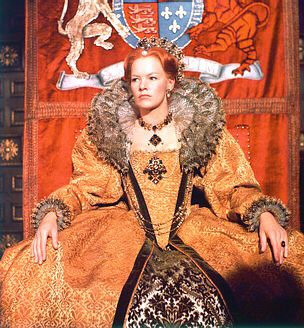 Queen Elizabeth 1st Film Costume    Queen Elizabeth 1st costume. Orange/gold brocade gown with black velvet ribbon decoration. Underskirt of black and white (flocked?) damask. Beautiful white and black ruffs at neck and wrists.    Worn by Glenda Jackson in 'Mary Queen of Scots'