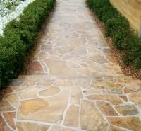 Crazy paving pathway lined with box hedge