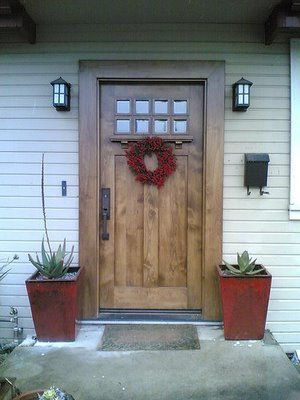 Exterior Doors | craftsman style front door accented with a red wreath and planters | Bayer Built Woodworks