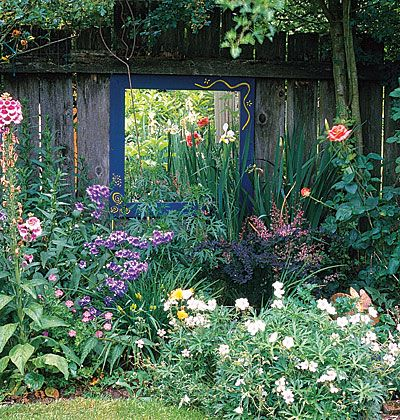 """An inexpensive way to brighten a dark corner is to hang a mirror that reflects light from sunnier parts of the garden.    Here, not only does the looking glass remedy a black hole, but it also makes plants and flowers seem to stretch into an adjacent space."""
