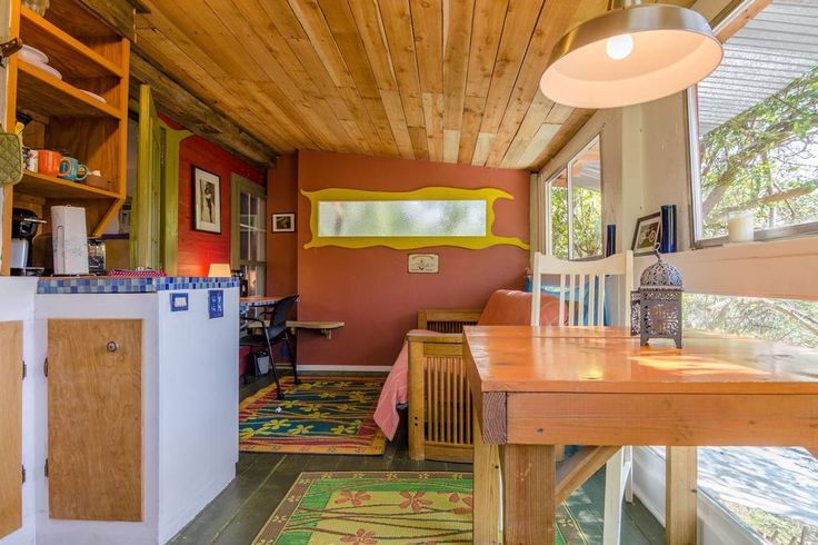 View of the kitchenette (left), eating table (right), Queen futon couch (far right), desk (far left)