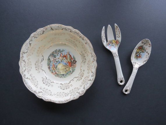Made in 1945 by Homer Laughlin, this is a vintage Virginia Rose salad bowl with the matching serving utensils. All of the pieces feature a Victorian couple scene with 22 kt. gold accents.  These would be great for formal occasions and would also make a thoughtful wedding gift!  CONDITION: Good vintage condition with no chips or cracks. There are a few spots of heavier glaze along the underside rim of the bowl. There is also a little yellowed spot in the glaze inside the bowl as well as a…