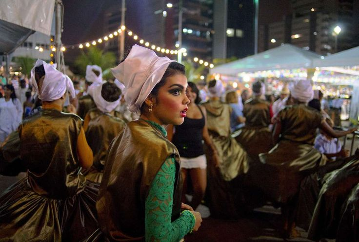 A Brazilian woman in a traditional costume looks on during a street festival beside a beach, where Ghana's national football team base camp is located for the 2014 FIFA World Cup in Maceio, Brazil on June 18, 2014. (CARL DE SOUZA/AFP/Getty Images)