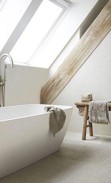 Dans cette salle de bain aménagée sous pente, pas d'artifice déco inutile ! Une baignoire balnéo, des murs blanc mettant en valeur les poutres blanchies, un tabouret en bois clair, tous les ingrédients sont réunis pour un bain zen
