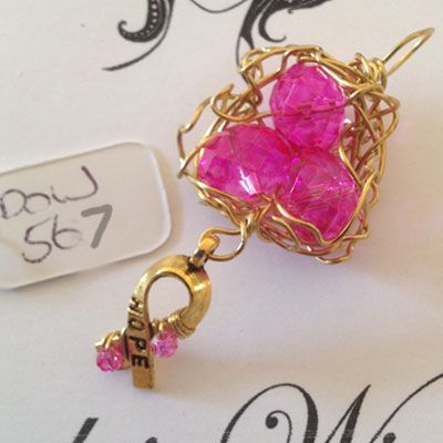 doinWire handcrafted gold craft wire birds nest, 3 bright pink crystals with Awareness charm wrapped with pink crystals. DOW567