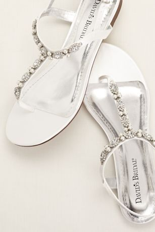 Pearl and crystal embellishment makes this t-strap sandal an elegant and comfortable option for any event!  Satin t-strap sandal encrusted with sparkling crystals and opulent pearls.  Available in White online only.  Fully lined. Imported.  Dyeable shoes are sold in White as shown. Bring your dyeable shoes to your local David's Bridal Store to have them dyed in any of our exclusive colors.