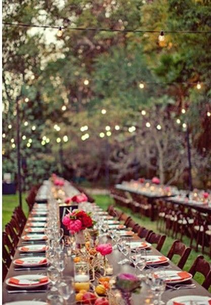 Long tables...soft lights...green grass...under the star light!  LOVE the different flower arrangements- bright colors, different vases and heights