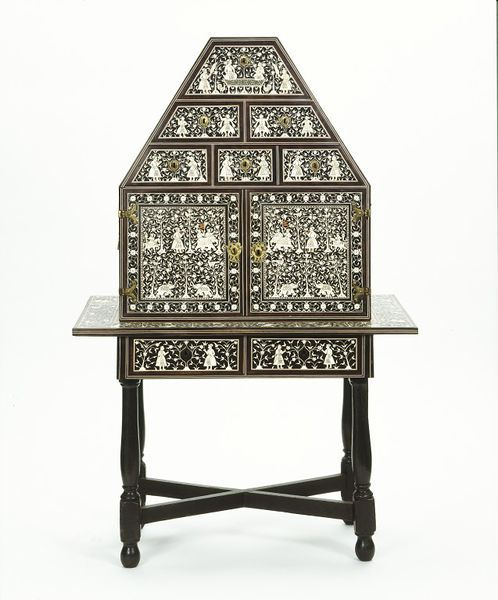 Cabinet on table-stand | V&A Search the Collections. This cabinet on table-stand is a superb example of Indian furniture. The maker has decorated the exterior with rich ivory inlay. It shows pairs of courtly figures engaged in various activities. These include conversing while seated on a platform throne (takht), dancing, and hunting with falcons and on elephant back. The decoration is typical of a large group of furniture which scholars believe originated in the coastal regions of Gujarat…