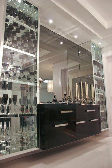 A cristaleira é um dos destaques da sala de jantar. Todo o volume foi revestido com espelho cristal, para valorizar o vasto conjunto de taça...