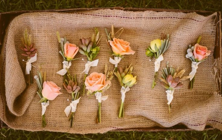An assortment of unique boutonnières for the groom and his groomsmen include spray roses, ranunculus, succulents, silver brunia and sea grass.