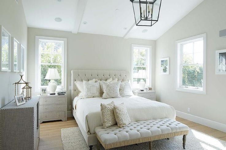 Monochromatic bedroom features a vaulted ceiling accented with a carriage lantern above a ...