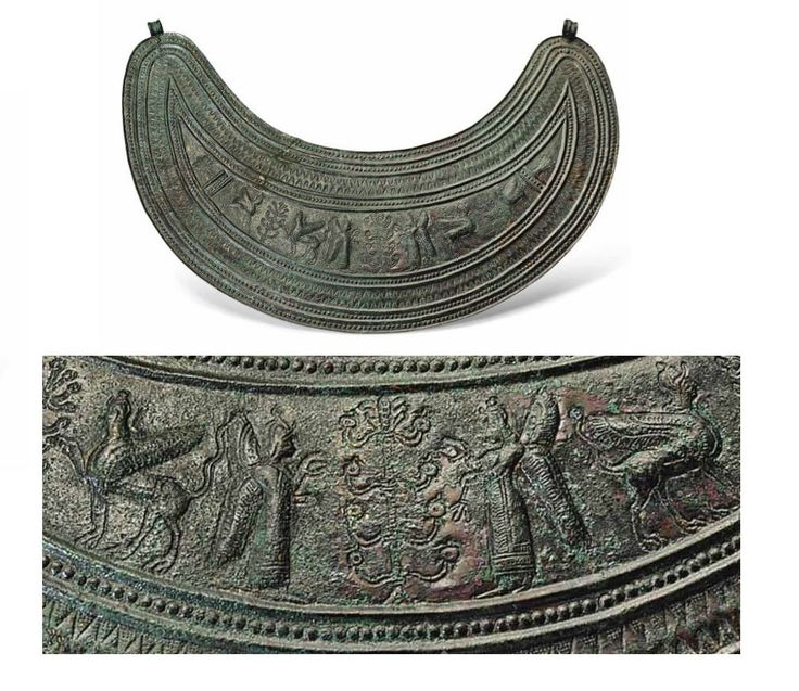 Urartian bronze pectoral, late 8th-7th century B.C. Of crescentic form, decorated in chased low relief with a central frieze centred by a stylised tree flanked by two standing winged deities, on either side another stylised tree flanked on either side by a standing winged bull, within a border of dots, zigzags and ridges, ribbed suspension hooks at the apexes, 20.8 cm wide. Private collection