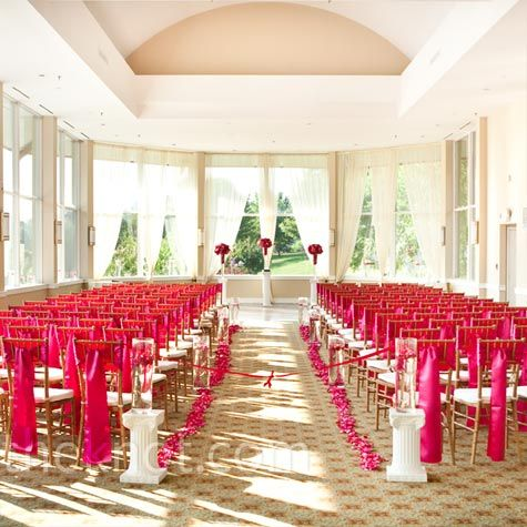 Rails of pink rose petals and tall vessels revealing submerged orchids create the aisle.