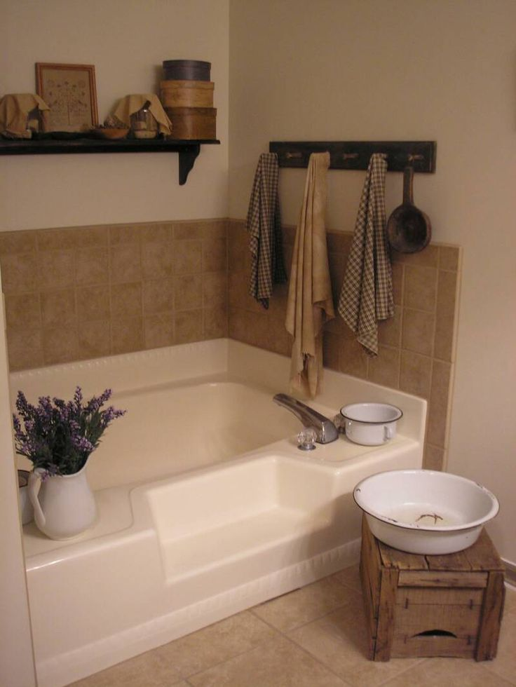 A Primitive Place ~ Primitive & Colonial Inspired Bathrooms.  This tub would look so much better with beadboard glued onto the front or a shower tension rod with the blue/beige fabric used for many of the valence/curtains in primitive design.