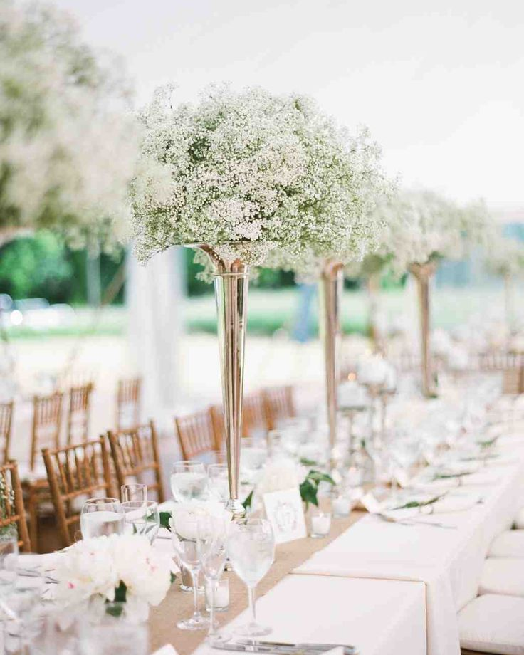 Affordable Wedding Centerpieces That Don't Look Cheap | Martha Stewart Weddings - These tall and abundant arrangements are as simple as they are beautiful, using bundles of low-cost baby's breath for a delicate but full look. The smaller glasses beneath can hold any inexpensive bloom, from carnations and chrysanthemums to hydrangeas and even roses.