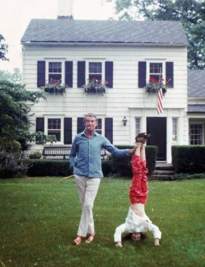 Society photographer Slim Aarons helps his daughter Mary to sustain a headstand, Bedford, New York, 4th July 1970.