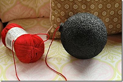 Using a Styrofoam sphere and a 2-liter bottle cap, I spray painted them with black chalkboard paint (don't use regular spray paint as it will disintegrate the Styrofoam…lesson learned). Glued the bottle cap and a skein of red yarn to the sphere