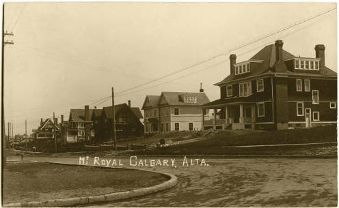 Black and white photograph of a residential street in the Mount Royal district of Calgary. The homes are large, on a paved road with curbs. Photo: Postcards From the Past, Calgary Public Library