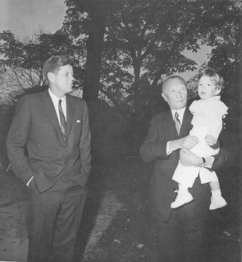 Germany's Chancellor Konrad Adenauer shows his skill as a grandfather scooping up John-John during a visit to Washington. A copy of this picture was given to Adenauer and he was so taken with it he sent Cecil Stoughton an inscribed pictorial biography of himself.