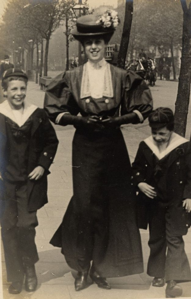 An elegantly dressed upper-class woman walking with her two sons along Cromwell Road