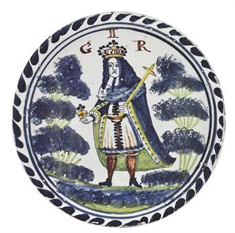AN ENGLISH DELFT BLUE-DASH ROYAL PORTRAIT CHARGER OF GEORGE II CIRCA 1725-1727, BRISTOL, JOSIAH BUNDY OR JAMES GAYNARD OF LIMEKILN LANE OR PERHAPS BRISLINGTON Painted in colours with the crowned King in his coronation robes holding his orb and sceptre flanked by the initials GIIR in iron-red and by two four-tiered blue-sponged trees with green branches on a striped, washed and sponged blue and green mound within a concentric double circle and blue-dash border, the underside with a tin glaze…