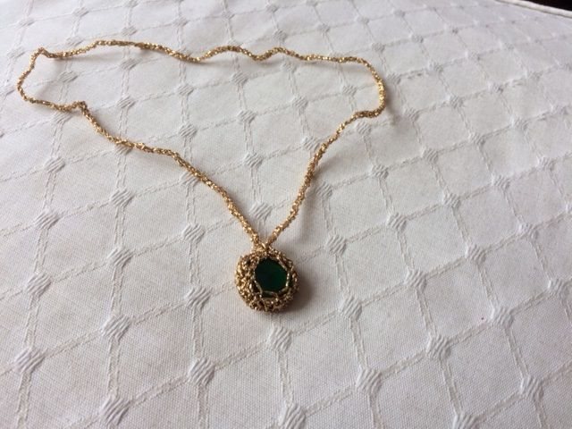 Crochet a necklace round a 'stone'. Make a magic circle, crochet eight doubles into circle, slipstitch to begining, two doubles into each stick (16) slipstitch to end, increase the ring until it's the same size as your stone. Put stone into crochet and decrease around until the stone fits neatly inside, then crochet a long chain.