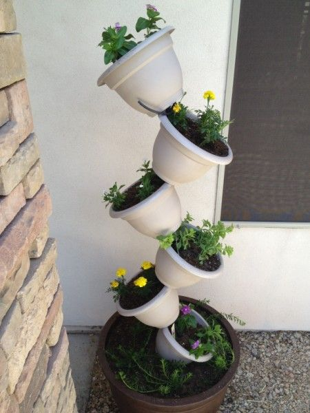DIY tipsy top vertical garden made from plastic or terracotta pots, flowers, and rebar.