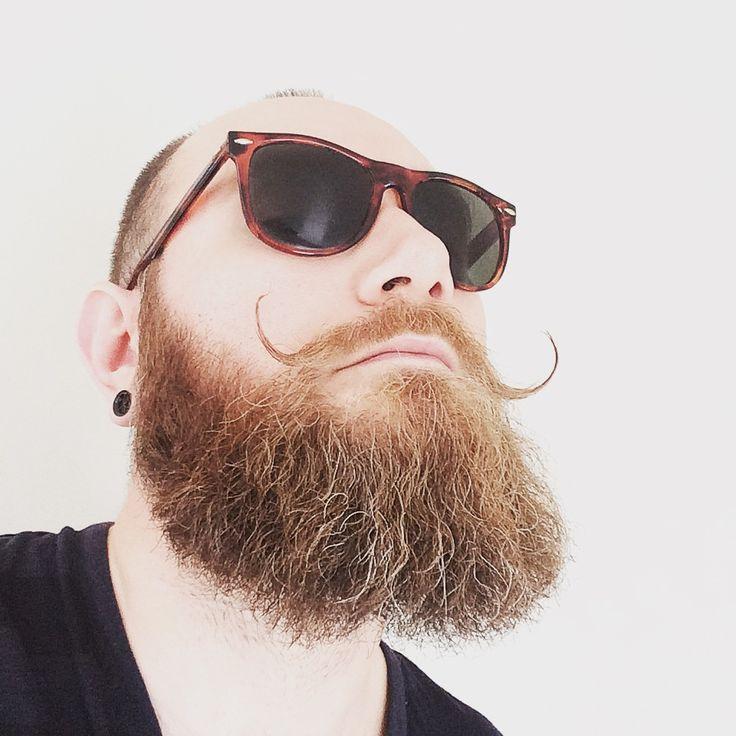Greying beard, sunglasses and a swirly mustache.