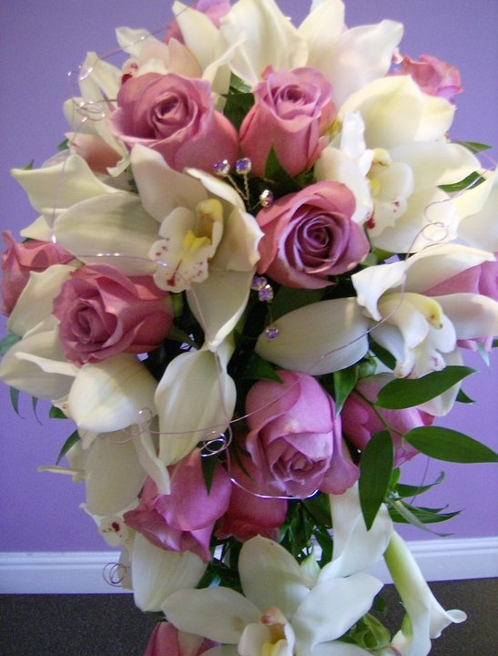 Roses, callas and cymbidium orchids in a teardrop shape