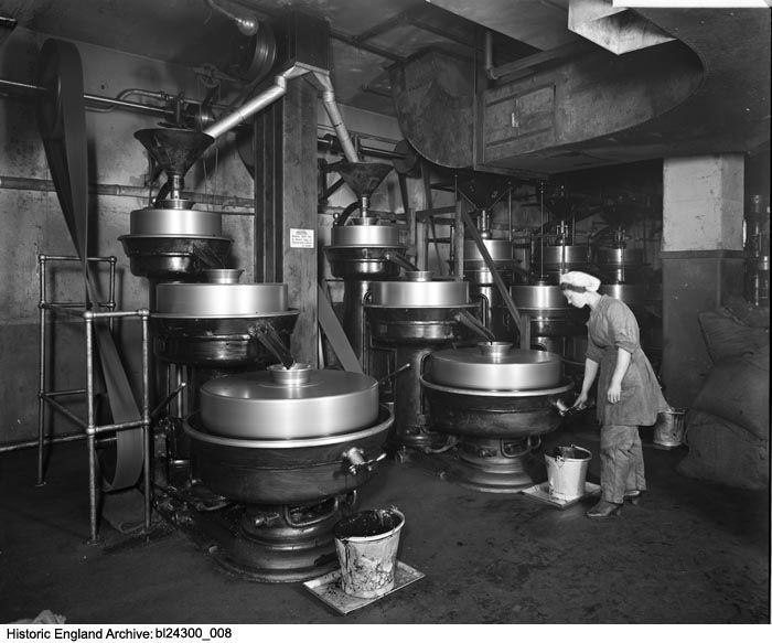 BL24300/008 A woman tapping chocolate liquor from a cocoa mill at the factory of J Lyons and Co., Cadby Hall, Hammersmith Road, London, W14.  During WWI women were employed in jobs left vacant by men fighting on the front. This photograph was taken for J Lyons and Co. who purchased Cadby Hall, a former piano showroom  in 1894. They occupied the site until the 1980s producing a wide range of foodstuffs. Date: Jul 1918 Photographer: Adolphe Augustus Boucher, Bedford Lemere and Company