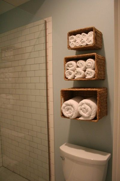 storage idea for small bathrooms.. baskets for towel holders or anything.
