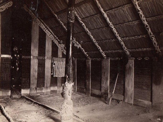 Interior of a wharenui (Maori meeting house) with carved and painted elements. 1880-1889