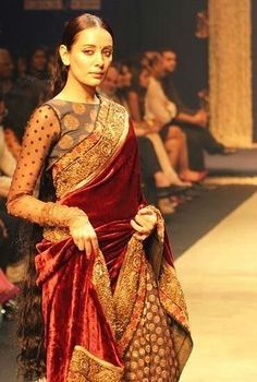 A unique long sleeve saree comprised with the colors of red, gold and hints of green.